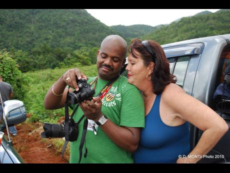 Photographer Michael Samuels shares a photo with fellow photographer Nicola Williams at a dirt rally event.