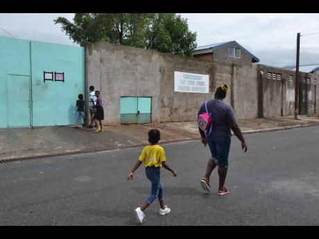 A woman and a child walk by the Missionaries of the Poor-operated Faith Centre in Kingston, which has recorded 74 COVID-19 cases.
