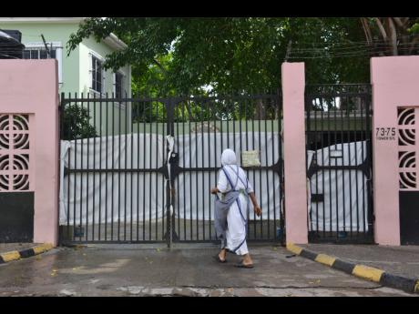 A sister walks towards the Mary Queen of Peace Missionaries of the Poor building at Tower Street, Kingston, on Monday. Charities run by the Catholic group have been hit by more than 160 cases of the coronavirus.