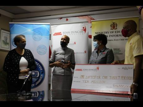 Education Minister Fayval Williams (second left) says thanks for the donation of $10 million from the Joan Duncan Foundation towards the Government's One Laptop or Tablet Per Child initiative after Tuesdays' presentation of a symbolic cheque at the com