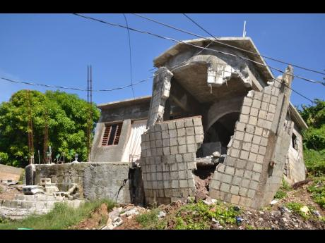 The collapsed walls of a house in Shooters Hill, St Andrew, present a stark reminder of the devastation wreaked in the eastern Jamaica community after rainstorms turned roads and yards into river courses on the weekend.