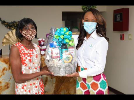 Ann Marie Clayton (left) accepts a gift basket from Melia McKitty Plummer.