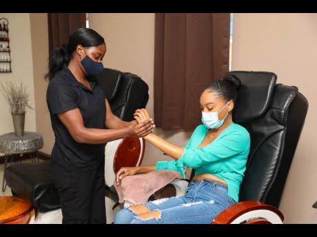 Toni Bennett gets a hand massage from nail technician Odette Barnett as part of her manicure.