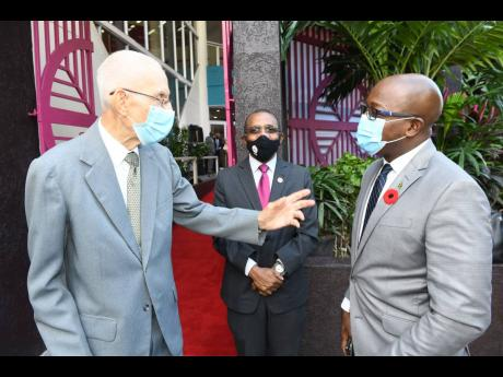 Minister of Housing, Urban Renewal, Environment and Climate Change, Pearnel Charles Jr (right), engages in conversation with Douglas Cover (left), former general manager, Victoria Mutual Building Society, as Courtney Campbell, president and CEO, Victoria M