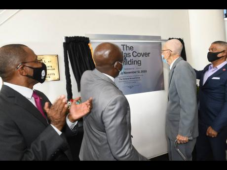 Courtney Campbell, president and CEO, Victoria Mutual Group, applauds, following the unveiling of the building plaque during the naming of Victoria Mutual's Duke Street head office. Also sharing in the moment are (from left) Michael McMorris, chairman, V