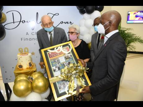 A champion of financial inclusion, Douglas Cover (left) is presented with a framed token during the official naming ceremony by Peter Reid (right), CEO, Victoria Mutual Building Society. Cover is joined by his wife,  Judith, and Pearnel Charles Jr .