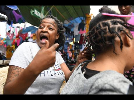 Nastassia Findley says the COVID-19 pandemic is set to ruin Christmas for her and her family. As she combed a customer's hair in downtown Kingston yesterday, she also lamented the cancellation of the year end fireworks on the Waterfront.