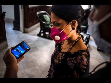 Wearing a mask to curb the spread of the new coronavirus, Cuban singer and composer Haydee Milanes watches a music video on a partner's mobile phone in Havana, Cuba. Milanes is one of many Cuban musicians who are turning to the Internet or seeking other