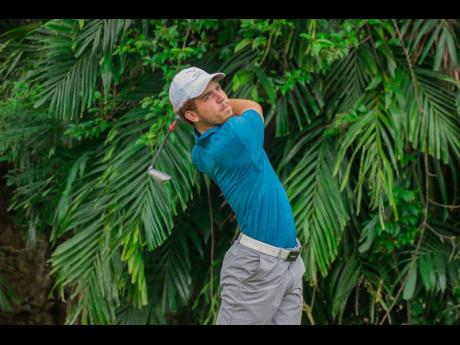 Justin Burrowes plays a tee shot during his round at the Alliance Buccaneers Memorial Golf Tournament at the Caymanas Golf course in St Catherine yesterday.