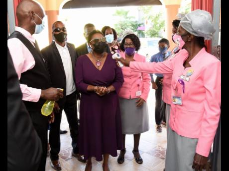 Olivia Grange, minister of gender affairs, has her temperature read and hands sanitised by members of Power of Faith Ministries in Portmore, St Catherine, before she entered the church. Sunday's church service kicked off commemoration of International Da