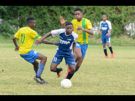 Cavalier's Javon Smith (second left) skips past Santos defender Jean-Marc Gayle (left) and drives forward in the Kingston and St Andrew Football Association Under 15 Championship finals at the Alpha Boys Field on Thursday, August 30, 2018.