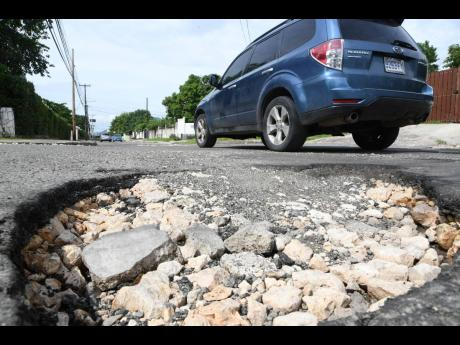 A motorist drives past a pothole on Elizabeth Avenue, off Red Hills Road, in St Andrew. Dozens of roads across Jamaica have been damaged by tropical storms Eta and Zeta.