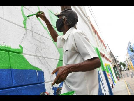 Artist John Elliott painting a mural as part of the Tourism Enhancement Fund, Sherwin-Williams and Kingston Creative-led art revival on Water Lane in downtown Kingston yesterday.