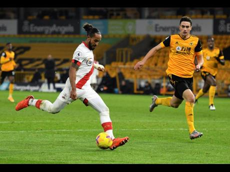 Southampton's Theo Walcott (left) attempts a shot on goal during their English Premier League match against Wolverhampton Wanderers at Molineux Stadium in Wolverhampton, England, yesterday.