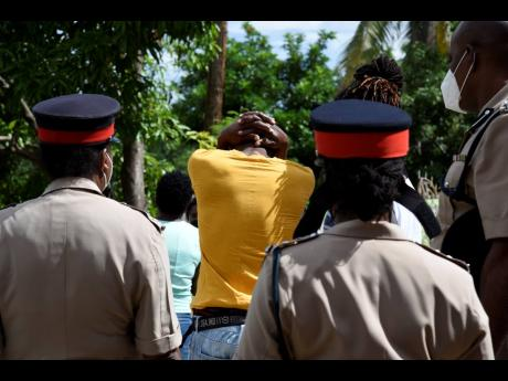 The distressed father of Christina and Mishane McFarlane walks along with police personnel in Tryall Heights, St Catherine, on Monday. The girls and their grandmother, Iciline McFarlane, were killed by gunmen on Sunday.
