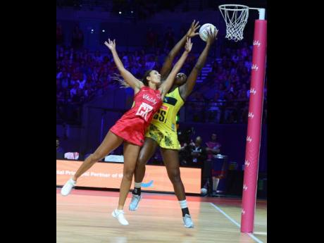 Sunshine Girls captain Jhaniele Fowler (right) outstretches England Roses goal keeper Geva Mentor to claim the ball, before scoring a goal during their Group G Vitality Netball World Cup match at the M&S Bank Arena in Liverpool, England, last July.