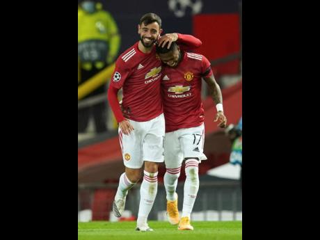 Manchester United's Bruno Fernandes (left) celebrates with Fred during the Champions League Group H match between Manchester United and Istanbul Basaksehir at Old Trafford in Manchester, England, yesterday. Manchester United won 4-1.