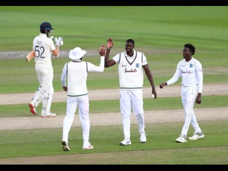 West Indies' captain Jason Holder (second right) celebrates with teammates the dismissal of England's Dom Sibley (left) during the third day of the third Test match at Old Trafford in Manchester, England, in July.