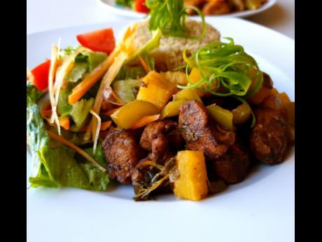 A view of the brown stew chicken breasts with pumpkin-quinoa and fresh salad.