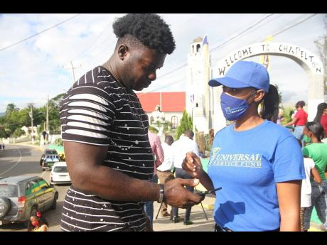 Camera Roberts of the Universal Service Fund assists Kenroy Johnson, a Clarendon resident, in connecting to free public Wi-Fi in Chapelton on December 10. Technology Minister Daryl Vaz pledged to deliver universal Internet service across Jamaica by 2025.