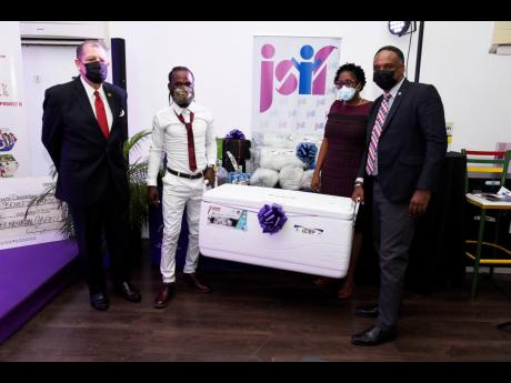 Fisherman Shawn Castell (second left) is presented with an igloo and fishing equipment by Jamaica Social Investment Fund Managing Director Omar Sweeney (right) yesterday as Industry, Commerce and Investment Minister Audley Shaw (left) and St Andrew South W