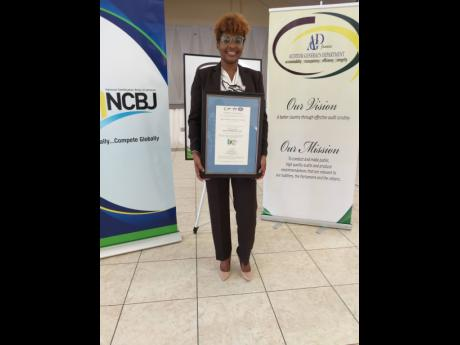 Auditor General Pamela Monroe Ellis displays the ISO 9001 certification received by her department Thursday after completing a two-year quality standards exercise with the National Certification Body of Jamaica.