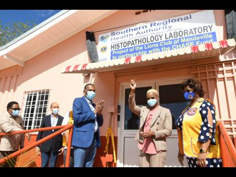 Dr Collette Hall (second right), regional pathologist, is elated after Wilford Heaven (centre), CEO of CHASE Fund, presented her with the keys to the new Histopathology Laboratory at Mandeville Regional Hospital on Thursday. Looking on from left are Alwyn