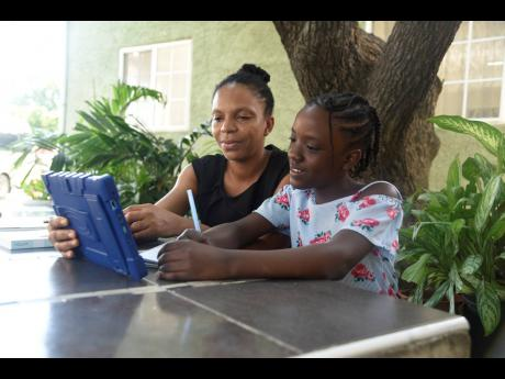 Abigail Garvey takes notes from the tablet she won in a Christmas jingle competition recently. Delia Garvey, Abigail's mother, said that she saw the competition poster in the school's WhatsApp group and allowed her daughter to give it a shot.
