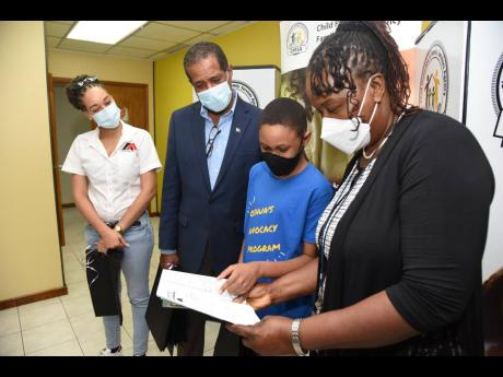 From left: Amashika Lorne, principal director of Amashika & Associates Limited, looks through of the colouring books with Factories Corporation of Jamaica Chairman Lyttleton Shirley; Jamaica College student Joshua Grey, founder of Joshau's Advocated Prog