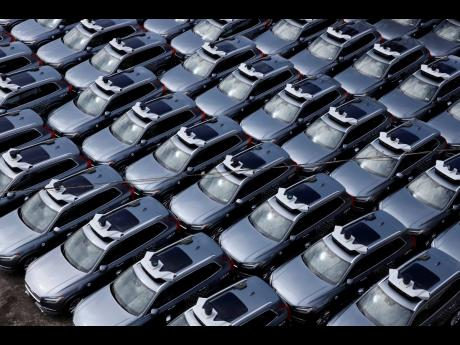 Below: This March 20, 2020 file photo shows a parking lot full of Uber  self-driving Volvos in  Pittsburgh.