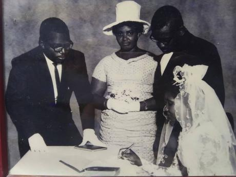 Best man Clunis Allen (left) and matron of honour Joyce Frazer look on as Reginald and Moreen Francis prepare to sign the marriage register.