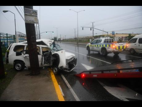 A wrecker prepares to transport a Toyota Probox motorcar which crashed into a light pole on Marcus Garvey Drive during heavy rainfall on Sunday.