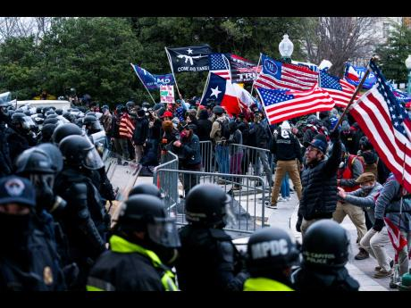 Supporters of President Donald Trump are confronted by U. Capitol Police officers outside the Capitol in Washington yesterday.