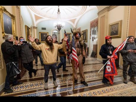 In this January 6, 2021 photo supporters of President Donald Trump are confronted by US Capitol Police officers outside the Senate Chamber inside the Capitol in Washington. Jacob Anthony Chansley, the Arizona man with the painted face and wearing a horned,