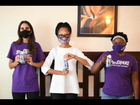 Lauren Mahfood (left), Marketing Manager of Trade Winds Citrus, Arlene Martin, Acting General Manager of Professional Football Jamaica and Keresha Ferguson, Marketing Coordinator, Trade Winds Citrus pose with bottles of Tru Shake after Trade Winds Citrus s