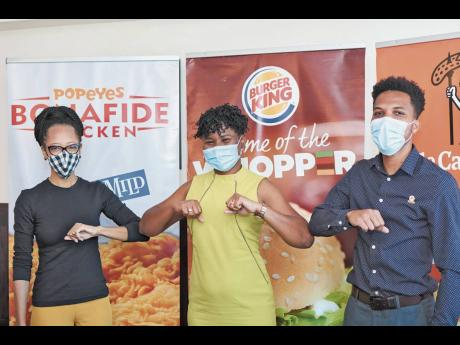 Arlene Martin (left), acting general manager, Professional Football Jamaica, touches elbows with Sabrena McDonald Radcliffe, head of sales and marketing at Restaurant Associates Limited (RAL), while Oshane Thoms, brand manager, Popeyes and Little Caesars P