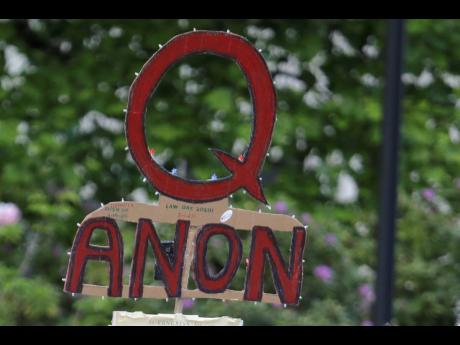 A person carries a sign supporting QAnon during a protest rally in Olympia, Washington, USA.
