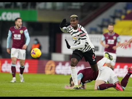 Manchester United's Paul Pogba (centre) controls the ball during the English Premier League match between Burnley and Manchester United in Burnley, England, yesterday. Manchester won the match 1-0.