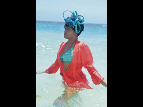 Aaliyah Campbell pairs her turquoise and red beachwear to swim in the 'Ocean' fascinator.