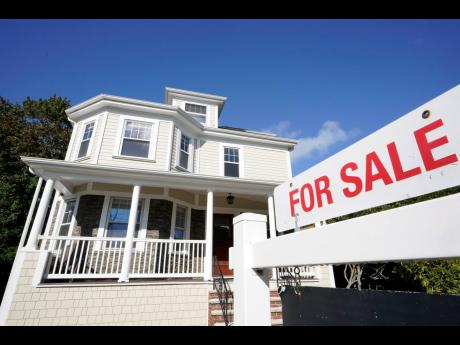 A for sale sign stands in front of a house on October 6, 2020, in Westwood, Massachusetts.