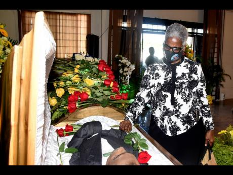 Kenyon Hemans/Photographer Widow Charmaine Maragh places a single red rose inside the coffin of her late husband and shipping stalwart, Harriat Maragh, during his funeral service at Romans Funeral Home on Dunrobin Avenue in St Andrew yesterday.
