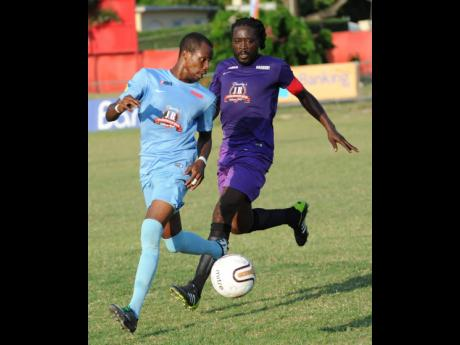 Central Kingston FC's Romario Davey (left) comes under pressure from Molynes United's Oniel Thomas during a KSAFA Major League match at the Barbican Field on Sunday, May 8, 2016. While Jamaica Football Federation's Technical Committee Chairman, Rudol