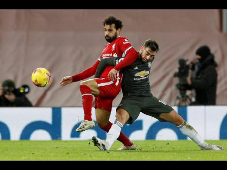 Manchester United's Bruno Fernandes fights for the ball with Liverpool's Mohamed Salah (left) during their English Premier League draw at Anfield Stadium, Liverpool, England, yesterday.