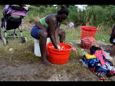 Elise Williams of Pleasant Hill, Linstea d washes clothes at the bank of Rio Cobre.