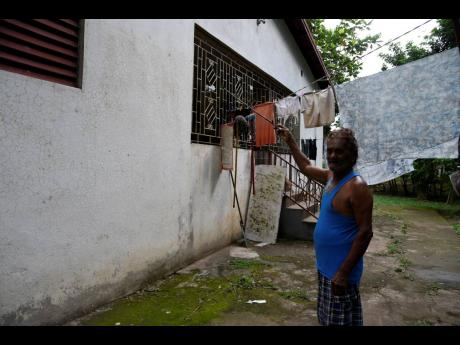 Sonny Mahabeer, a resident of Sunnyside, shows the mark where the flood waters from Rio Magno reached in 2017.