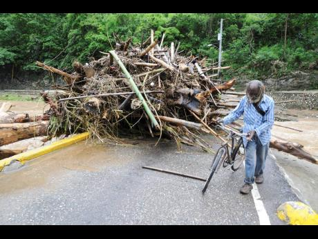 A cyclist makes his way past debris dumped on the Flat Bridge in Bog Walk, St Catherine by Rio Cobre.
