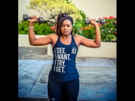 Working her muscles in a military press, Sagicor Life financial adviser Sia Garwood models this racerback shirt made from a special blend that keeps you dry.