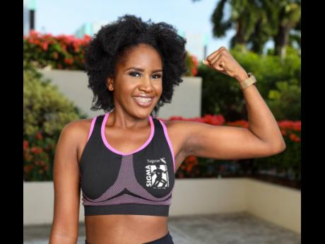 Sagicor Sigma Run Secretariat associate Alice Green shows her guns while displaying the Sigma Run sports bra.