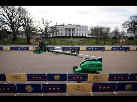 Workers make preparations on Tuesday, Janaury 19, on Pennsylvania Avenue in front of the White House for President-elect Joe Biden's inauguration ceremony, scheduled for Wednesday, January 20, in Washington.