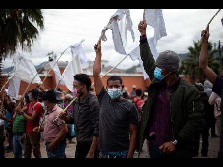 Honduran migrants raise white flags as they are blocked by Guatemalan soldiers and police from advancing towards the US border, on the highway in Vado Hondo, Guatemala, on Monday.